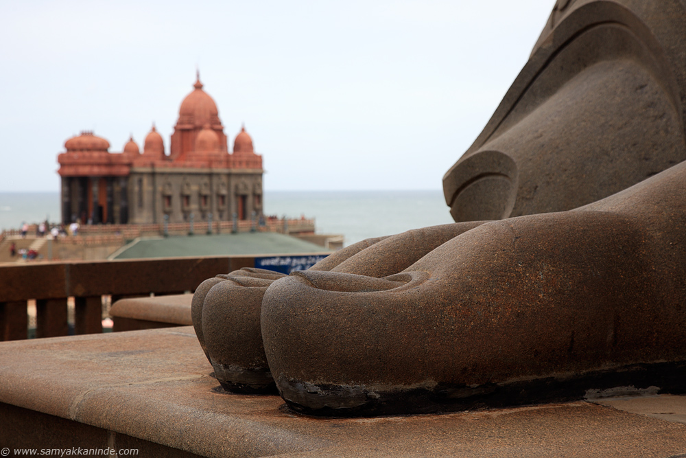 The feet fingers of Thiruvalluvar statue and vivekanada rock memorial in background.